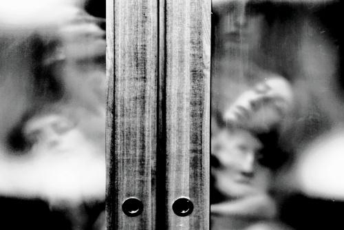 """Dietro la porta - © Paola Tornambè - Una porta - accesso e separazione. Un confine tra due mondi. Il dentro e il fuori; l'interiorità e l'esteriorità; il benessere e la follia; la vita e la morte. Ma la separazione è davvero così netta? La porta si apre e si chiude. Una scelta, varcare la soglia. Una scelta, rimanere dentro. L'alternativa è seguire la luce che esula da quella condizione e conduce fuori. Forse i due mondi non sono poi così separati. Un confine mentale, labilissimo, evanescente come le anime, trasparente come il vetro di cui questa porta è fatta. Fotografia selezionata da F-Stop Magazine nel 2019 per """"Alternative Portrait""""."""